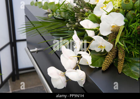 A flower arrangement on a coffin in a mortuary - Stock Image