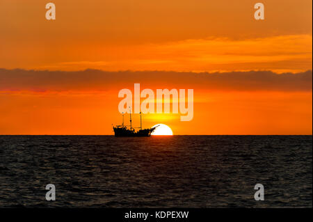 Ship pirate silhouette is a pirate ship sitting at sea watching the ocean sunset silhouetted against the sun.. - Stock Image