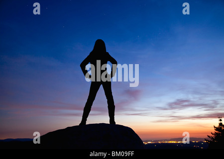 Silhouette of a woman standing on a rock at night overlooking the city lights - Stock Image