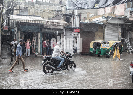 A motorcycle trying to pass in a flooded street in the monsoon rain in New Delhi, India - Stock Image