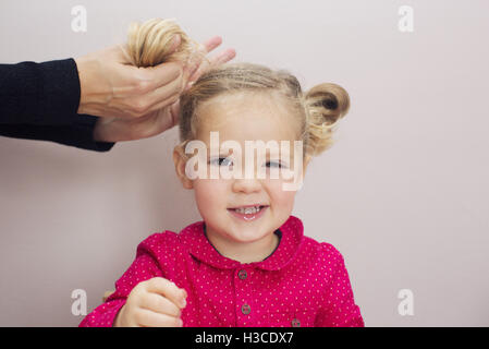 Little girl having her hair arranged in pigtails - Stock Image