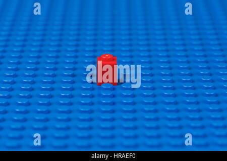 A single Lego piece on a blue Lego base plate. - Stock Image