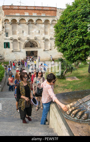 Split, Croatia. Asian female tourist is rubbing the toe of the Statue of Grgur Ninski, Bishop Gregory of Nin - it is said to bring good luck. - Stock Image