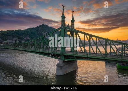 Budapest, Hungary - Beautiful sunset over River Danube with Liberty Bridge, Gellert Hill and Statue of Liberty at background - Stock Image