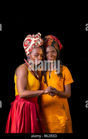 An African mother and daughter holding hands against a black background - Stock Image