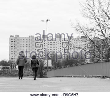 Poznan, Poland - December 2, 2018: Couple walking on a bridge on the Orla Bialego district with apartment block in the background. - Stock Image