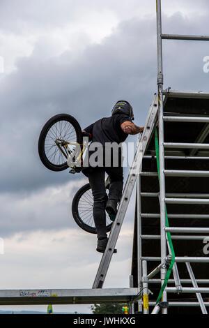 Bielsko-Biala, Poland. 12th Aug, 2017. International automotive trade fairs - MotoShow Bielsko-Biala. Man going upstairs with bike. Credit: Lukasz Obermann/Alamy Live News - Stock Image