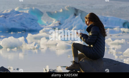 Profile view of woman using cell phone in remote landscape near frozen glaciers in still ocean - Stock Image