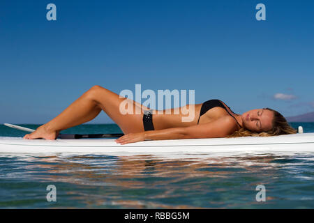 Healthy, fit woman relaxes on stand up paddle board at Napili Bay, Maui, Hawaii. - Stock Image