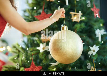 Closeup on young woman in red dress near Christmas tree hanging big gold Christmas ball - Stock Image