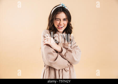 Image of a beautiful happy young woman posing isolated over beige wall background. - Stock Image