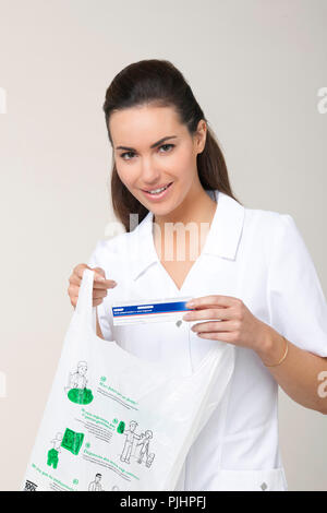 Woman pharmacist putting box of a vaccine against influenza in a bag - Stock Image