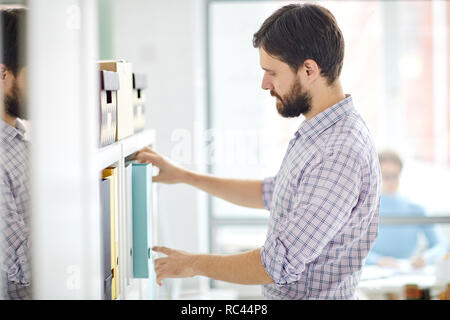 Bearded businessman taking one of folders with archive data from shelf while looking for some particular financial documents - Stock Image