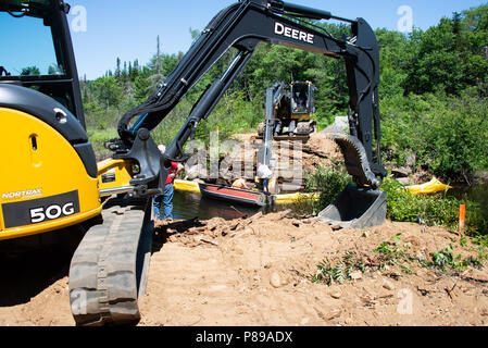 Two track hoe machines and three workers building a new logging bridge over the Kunjamuk River in the Adirondack Mountains, NY USA - Stock Image