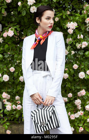 Woman in white linen culotte suit standing by flowering bush - Stock Image