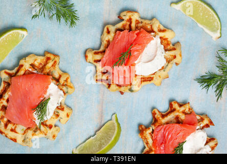 potato waffles with salmon, cream cheese on a blue wooden background. view from above - Stock Image