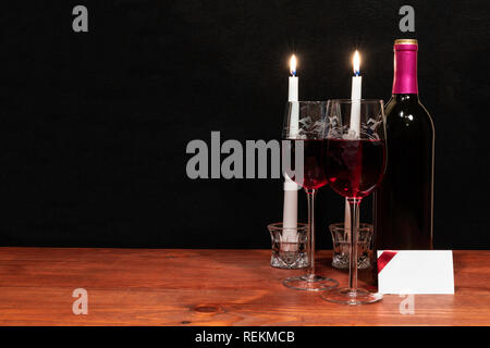 Beautiful etched wine glasses and bottle of red wine, white candles, on wooden table with name tag on dark background. Valentines, Mothers Day, Easter. - Stock Image