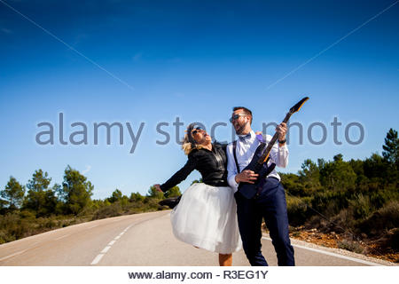 Rock bride with black leather jacket, boots and sunglasses poses with her boyfriend who plays an electric guitar in the middle of a lonely road. - Stock Image