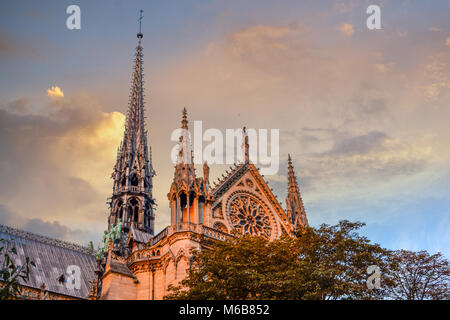 The exterior side and spires of the Notre Dame Cathedral in Paris France as the sun sets with the apostle statues - Stock Image