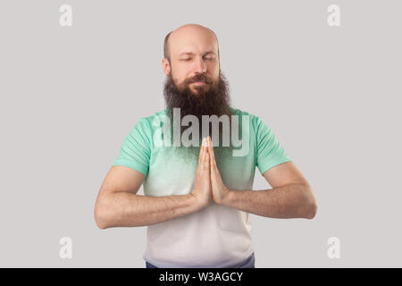 Portrait of calm serious middle aged bald man with long beard in light green t-shirt standing with closed eyes, palm hand and doing yoga meditation. i - Stock Image