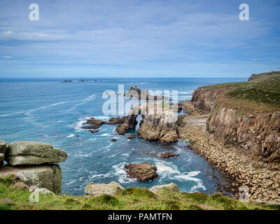 Rocky coastline of Lands End, Cornwall, UK, with the arch, Enys Dodnan, and the rock formation The Armed Knight, with the Longships Lighthouse offshor - Stock Image