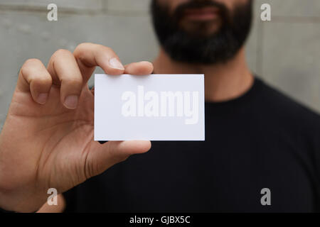 Bearded Man Wearing Casual Black Tshirt Showing Blank White Business Card.Blurred Background Ready Corporate Private - Stock Image