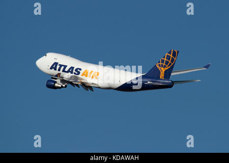 Atlas Air Boeing 747-400F cargo jet plane in flight against a blue sky. Air freight transport and supply chain management. - Stock Image