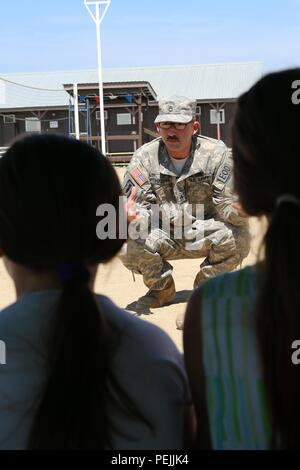 Staff Sgt. Brian Harris, an Alabama National Guard Soldier deployed to Kosovo with the 666th Explosive Ordnance Company out of Jacksonville, Ala., explains the danger of unexploded ordnance to a group of 50 students between the ages of 7-13 during an Aug. 29, 2015, visit by Pristina's A&A Language Center to Camp Bondsteel, Kosovo. During the visit, U.S. Army Soldiers held demonstrations, engaged the students in workshops and relationship-building exercises, and helped them better understand the multinational troops' mission as part of NATO's peace support effort in Kosovo. The A&A Language Cen - Stock Image