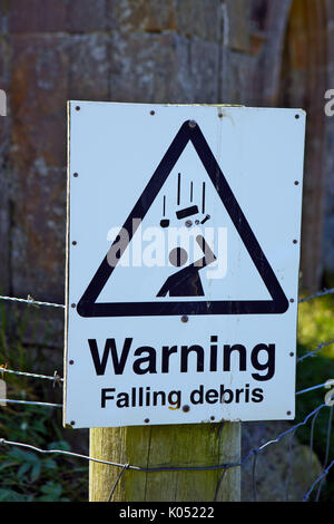 Warning falling debris sign at a dangerous unstable building - Stock Image