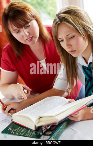 parent helping daughter girl with homework and coursework - Stock Image