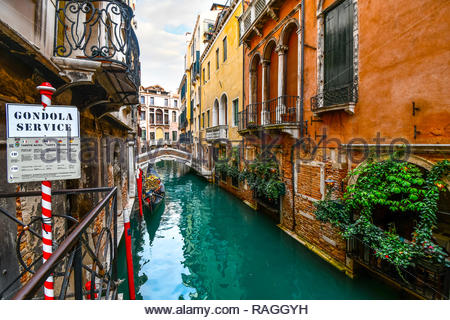 A gondolier waits for tourist customers at a gondola service point, on a picturesque canal in Venice, Italy - Stock Image