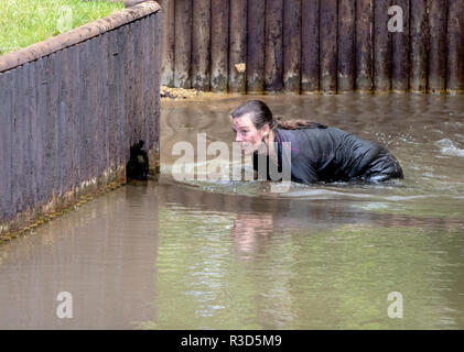 Rather soiled lady mud runner around a water crossing - Stock Image