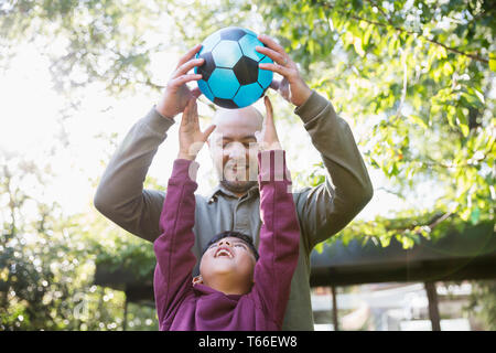 Father and son playing soccer in sunny park - Stock Image