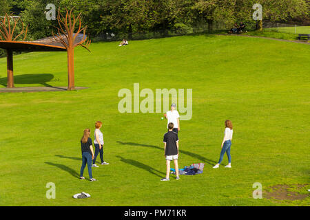 Group of five young people playing catch with a small ball in the open space of The Glebe, Bowness-on-Windermere, Cumbria. - Stock Image