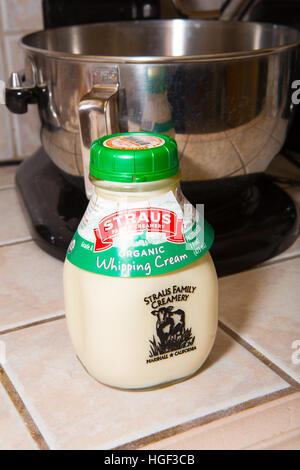 Organic whipping cream in a reusable glass bottle that has a refundable deposit - Stock Image