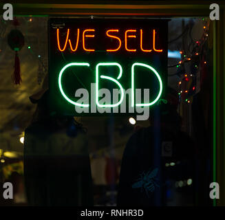 ASHEVILLE, NC, USA-2/16/19: A store advertises cannabidiol with red and green neon signs. - Stock Image
