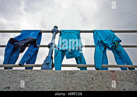 Hung out to dry, a collection of wetsuits adorn the promenade railings as their owners dry off. - Stock Image
