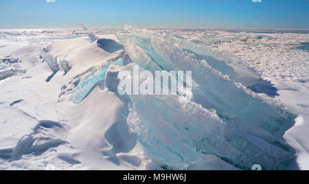 Snow and blue ice formations stacked up on the frozen lake surface of Georgian Bay, Ontario, Canada - Stock Image