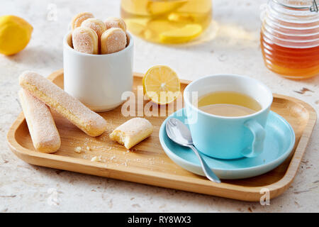 Sponge finger biscuits served with a cup of tea on wooden tray. - Stock Image