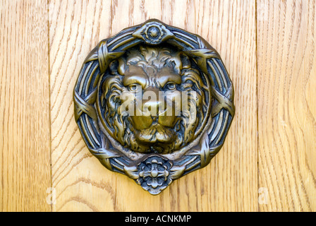 Brass door knocker in the form of a lions head on a wooden door at Amaravati Buddhist Monastery England Great Britain - Stock Image