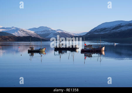 Fishing boats reflections moored in Loch Broom, Ullapool, with snowy winter mountains in the background - Stock Image