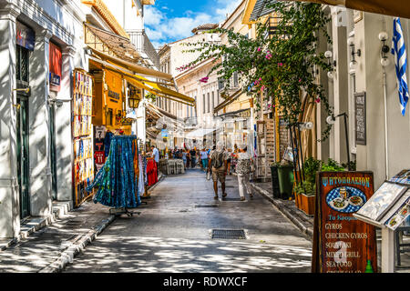 Athens, Greece - September 22 2018: Tourists walk the streets lined with souvenir shops and outdoor sidewalk cafes in the touristic Plaka section - Stock Image
