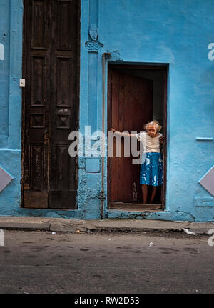 An old woman opens her front door to a back street of Havana, capital of Cuba - Stock Image