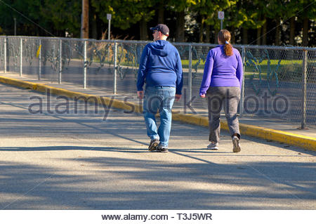 Middle-aged, overweight couple walking away on a fence lined street. - Stock Image