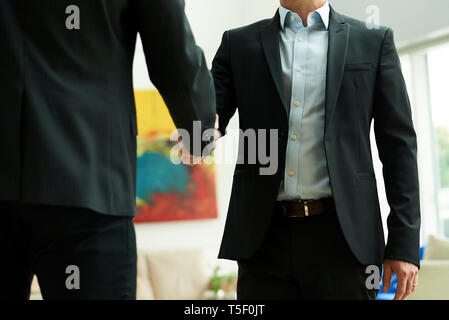 Mid section of businessmen shaking hands in office lobby - Stock Image