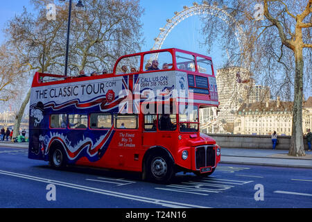 A bright red open roof tour bus drives along Victoria Embankment with the London Eye visible behind it as it shows London's landmarks and signts - Stock Image