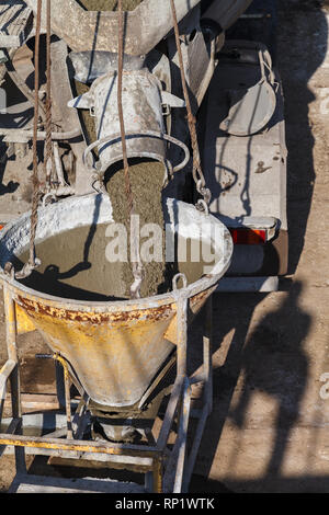The mixer truck pours liquid concrete into the construction crane bucket at the site of the house under construction - Stock Image