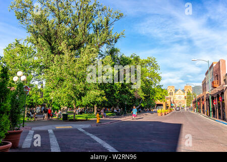 Santa Fe, USA - June 14, 2019: Old town street and plaza park in United States New Mexico city with adobe style architecture and church - Stock Image