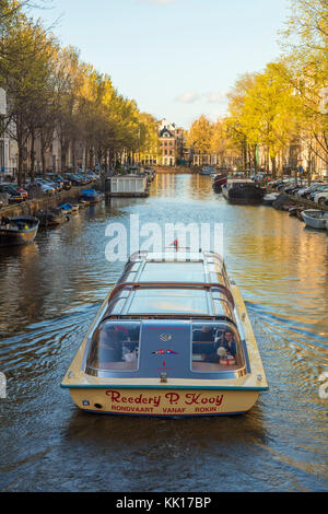 Pleasure boat on canal, central Amsterdam, The Netherlands - Stock Image