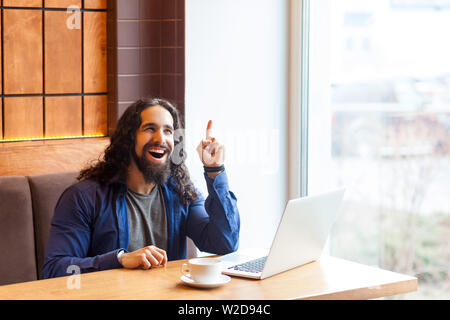 I have idea! Portrait of happy confident handsome young adult man freelancer in casual style sitting in cafe with laptop, showing finger up with tooth - Stock Image